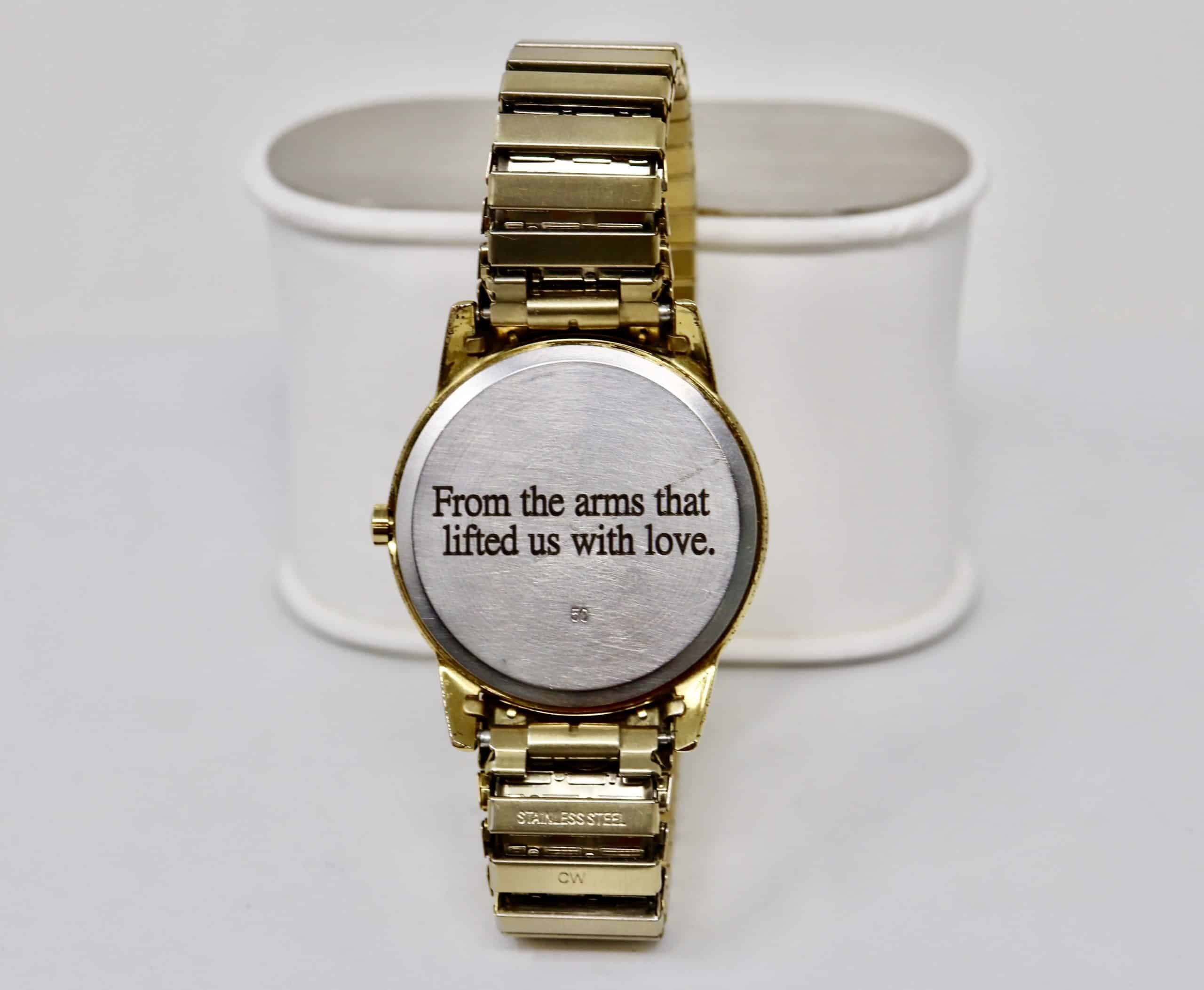 gold watch displaying back print that says from the arms that lifted us with love