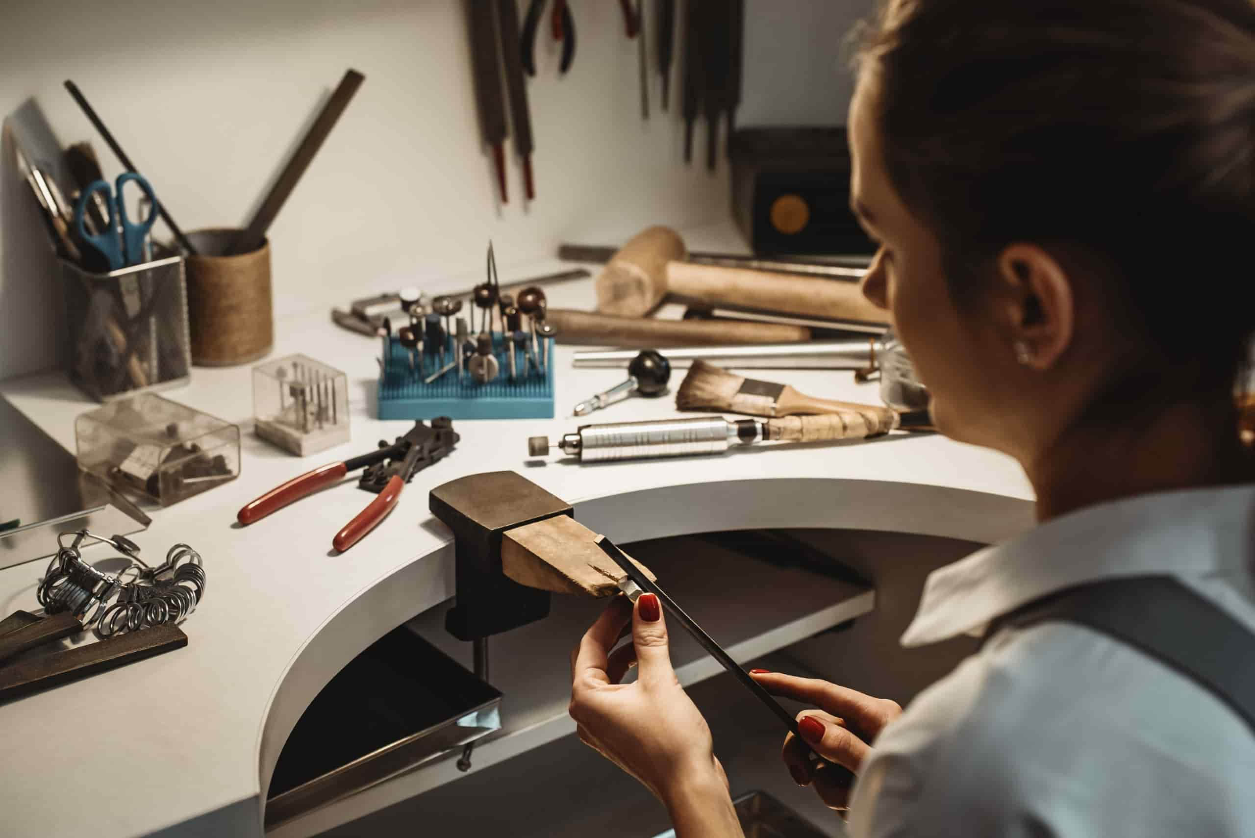 jeweler filing ring at work station surrounded by tools