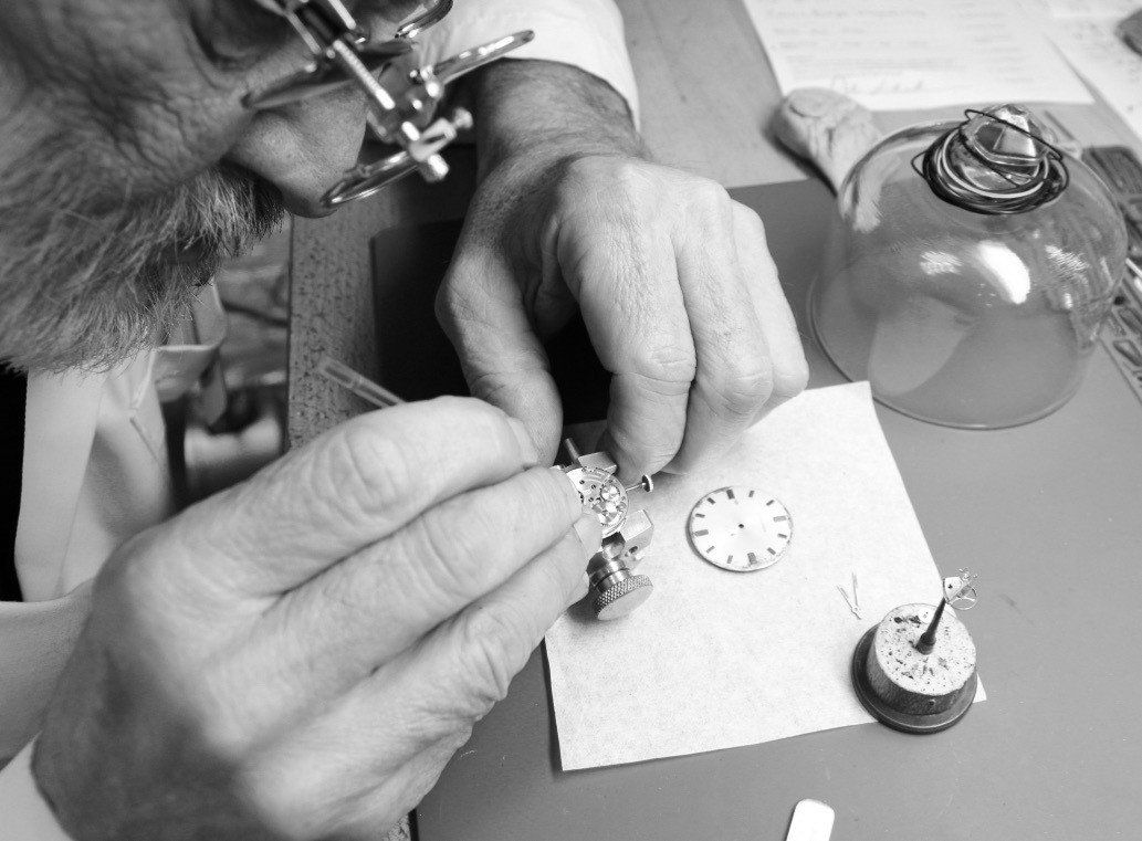 jeweler leaning on desk adjusting watch with screwdriver in watch movement holder